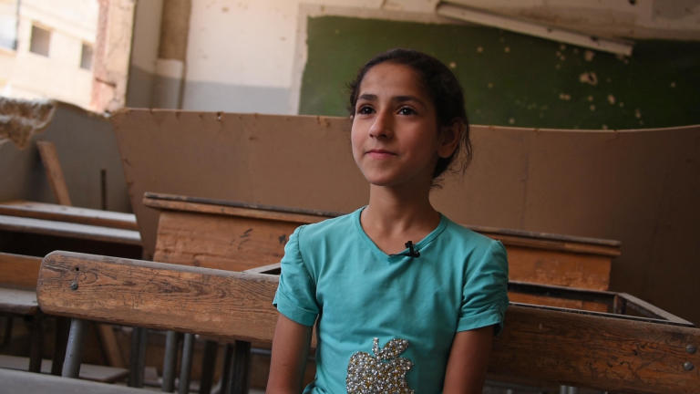 "Reem, 10, from Harasta, Eastern Ghouta ""My name is Reem and I'm from Harasta. I'm 10 years old. I always come to school so that I learn.  ""We didn't use to come to school, we were afraid of the missiles and used to stay in the basement. Even when I was in the basement I used to study. I had books and I used to study. I studied Arabic and Maths; I only had books for these two subjects with me. ""My two siblings died, it is only me and my parents now. ""My mother doesn't like if I get low grades so she keeps teaching me so I am always the first in class. ""I used to hide whenever there was a missile launched. I was very scared. One time there was a missile that hit the basement next to us. I was terrified. I am still scared now. ""I hope the situation becomes calm just like here with no bombings or airstrikes hitting us. ""I hope we can see the school without any damages or broken walls."" Photo: Karl Schembri/NRC"