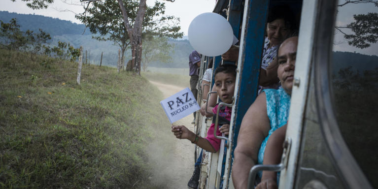 "February 6, 2016. North Caquetá department. A child waves a white flag with the writing ""Peace"" on it. With his family, he comes back from a ""peace pedagogical"" meeting at El Para village where peasant organizations presented and explained the peace talks between the FARC guerrilla and the Colombian government at Cuba. After four years of negotiations and a first peace deal signed at end of September 2016, Colombia entered into an unexpected period when 50,22% of the referendum voters rejected the agreement on October 2. Some days after, the president Juan Manuel Santos received the Nobel peace prize. The negotiators began a new round to adapt the agreement with some ""No"" positions and a new peace was approved by the congress on November 24. Photo credit: Nadège Mazars"