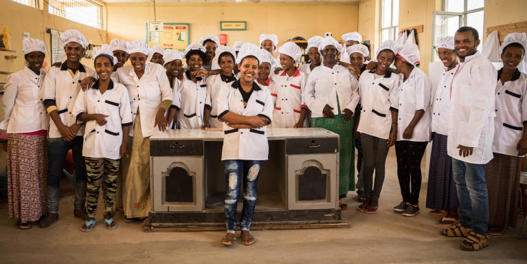 "Eden Tedros, 20 years old, from Eritrea, posing with her cooking class  in Hitsats refugee camp, Ethiopia.  ""I want to travel to Europe, but I want to travel safely,"" says 20-year-old Eden Tedros.   She tells us that a growing number of young Eritreans choose to leave their home country. Tedros is one of many who left in fear of spending her whole life in the military.  Tedros has lived as a refugee in Hitsats refugee camp in northern Ethiopia since June 2017. The closest city is far away and the refugees survive on food and water rations.  For many children and youth in Hitsats refugee camp, it's hard to imagine a future in Ethiopia. Four out of ten refugees leave Shire after three months. But Tedros has an opportunity to live out her dream.  She is studying to become a certified chef at NRC's youth education centre in Shire.  ""My biggest dream is to work in a restaurant in Europe.""   Many young Eritreans opt to leave their home country through dangerous migration routes to escape poverty.   But Tedros is hesitant to travel the seaway across the Mediterranean.  In 2017, over 300,000 refugees and migrants drowned during their attempt to cross the ocean.  ""I don't think I will travel the dangerous route.""  Photo: Beate Simarud/NRC Facts and figures:  Eritreans are the third largest group of refugees living in Ethiopia, with 37,321 refugees currently registered in refugee camps in the Shire area camps.   Currently there are 163,281 Eritrean refugees in Ethiopia.  It is estimated that nearly 40 per cent of Eritrean refugees leave the camps within the first three months of arrival, and 80 per cent leave within the first year, with significant numbers of the population departing irregularly from Ethiopia to third countries – often with the assistance of smugglers and at great risk to their lives.   The population in the Shire camps is unique, with a large number of children below the age of 18 and unaccompanied children.   As of June 2017, 72 per cent of the refugees living in Shire were under the age of 18, including 4,725 unaccompanied and separated children, representing approximately 11.5 per cent of the total refugee population.   Unaccompanied and separated children live in a variety of care arrangements, including community care, foster care, or family-based care."