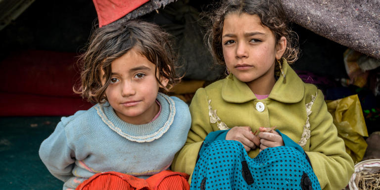 From right to left: Naseema, 9, Gul Ghotay's second daughter and Naseema's friend Latifa (in blue) inside their makeshift home in Feristan IDP settlement. PHoto: NRC/Enayatullah Azad
