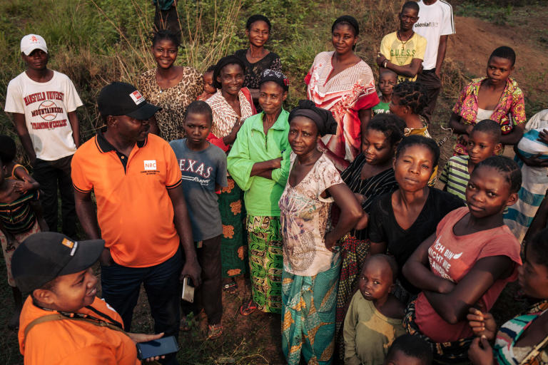 "NRC team meeting with residents of Mbulungu village.   Nearly 17,000 people—or close to 95 per cent of Mbulungu's population was forced to flee into the forest when fighting broke out between armed groups in March and April of 2017.  Some had to walk up to seven days to find a safe place to hide.  Many lost family members, were assaulted and nearly starved to death while on the move.  All lived in horrific conditions not certain of whether or not life would ever return to normal.  Though calm has returned to Mbulungu and several villages and towns just like it across Kasai-Central, people are not able to continue their lives as normal.  The violent conflict of 2017 left mass destruction in its wake—homes, markets, schools, sanitation facilities and health infrastructure in complete disarray.  In fact, 67 per cent of families living in Mbulungu do not have access to proper latrines and 55 per cent have no access to soap.  These absence of these basic necessities coupled with malnutrition and lack of proper shelter can lead to a host of diseases and death.  For that reason, NRC visited Mbulungu, in early 2017, where they met with the community to understand their primary needs.  NRC used its ""community-based approach"" by consulting with these communities to better understand their primary needs, to properly target the most vulnerable people and facilitate their ability to choose the assistance they require.  This intervention, however, is only a drop in the ocean of the vast needs of this community.  NRC is currently the only humanitarian actor in the zone and funding is not enough to address other acute needs such as food assistance, household items and education.  The Humanitarian Response Plan is currently only 25 per cent funded eight months into the year.  Humanitarian capacity is critically low.  If donors do not act now for the people of Mbulungu and for the rest of DR Congo, it will be too late.  August 29, 2018, Kasai-Central Province, DR Congo.  Photo: NRC/Aléxis Huguet"