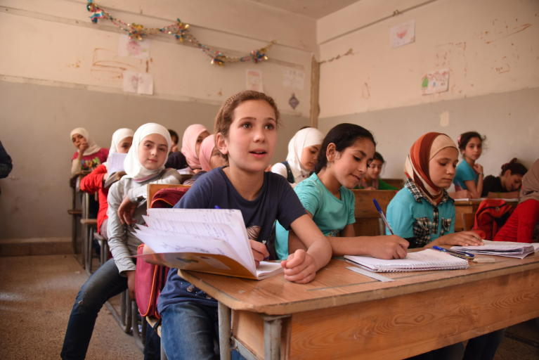 Raghad and Reem (left and centre), both 10, attend classes at Harasta School in Eastern Ghouta after months of living in basements and under siege. Photo: Karl Schembri/NRC