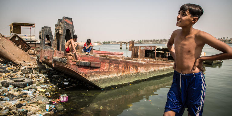 "The youth enjoy swimming and fishing in Basra's main river. Entire groups spend their time by the river, having fun in the middle of waste and rusty shipwrecks.  Khalid says, ""We all know someone who is sick because of the water, but what can we do? There is no clean water in the city, we have no options.""  Photo: Tom Peyre-Costa/NRC"