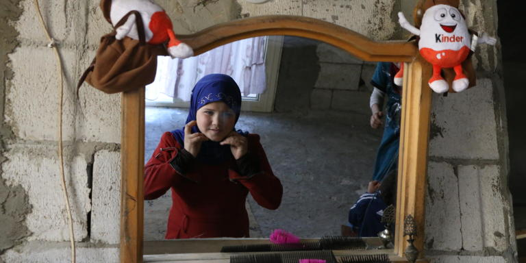 Sarah, 10, is fixing her veil on the mirror hung on the wall of their new shelter.  Photo: Nadine Malli/NRC